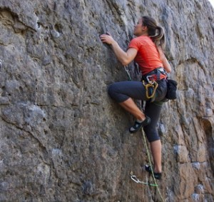 A young woman with a rope engaged in the sports of rock climbing on the rock.